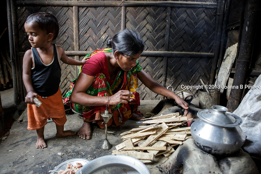 Adult woman in urban slum in Bangladesh preparing to cook over a traditional wood burning stove.