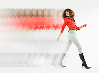 Woman with curly hair walking  in studio multiple exposure