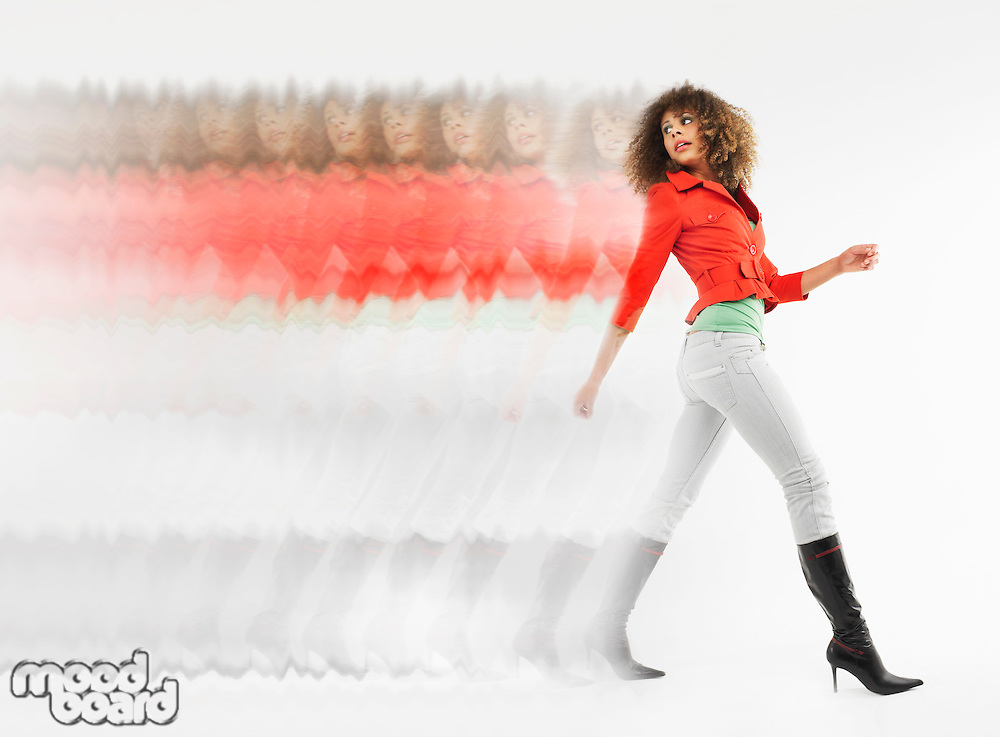 Woman with curly hair walking  in studio multiple exposure