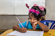 04 MARCH 2014 - MAE SOT, TAK, THAILAND: A girl works on a test at the Sky Blue School in Mae Sot. There are approximately 140 students in the Sky Blue School, north of Mae Sot. The school is next to the main landfill for Mae Sot and serves the children of the people who work in the landfill. The school relies on grants and donations from Non Governmental Organizations (NGOs). Reforms in Myanmar have alllowed NGOs to operate in Myanmar, as a result many NGOs are shifting resources to operations in Myanmar, leaving Burmese migrants and refugees in Thailand vulnerable. The Sky Blue School was not able to pay its teachers for three months during the current school year because money promised by a NGO wasn't delivered when the NGO started to support schools in Burma. The school got an emergency grant from the Burma Migrant Teachers' Association and has since been able to pay the teachers.    PHOTO BY JACK KURTZ