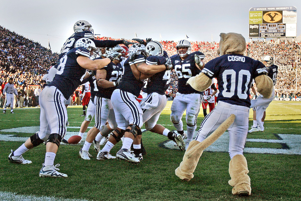 Brigham Young University players crowd around Brigham Young runningback Harvey Unga (45)  after he scored the winning touchdown to lead the Cougar over the Utes 17-10 in football at Lavell Edwards Stadium in Provo, Utah Saturday, Nov. 24, 2007.  August Miller/ Deseret Morning News .