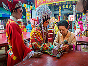 18 JANUARY 2015 - BANGKOK, THAILAND: A member of the community accompanied by performers wth the Sai Yong Hong Opera Troupe make on offering during performance at the Chaomae Thapthim Shrine, a Chinese shrine in a working class neighborhood of Bangkok near the Chulalongkorn University campus. The troupe's nine night performance at the shrine is an annual tradition and is the start of the Lunar New Year celebrations in the neighborhood. The performance is the shrine's way of thanking the Gods for making the year that is ending a successful one. Lunar New Year, also called Chinese New Year, is officially February 19 this year. Teochew opera is a form of Chinese opera that is popular in Thailand and Malaysia.             PHOTO BY JACK KURTZ