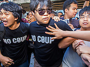 """14 FEBRUARY 2015 - BANGKOK, THAILAND:  Anti-coup protestors scuffle with supporters of the military government during an anti-coup protest in Bangkok. Dozens of people gathered in front of the Bangkok Art and Culture Centre in Bangkok Saturday to hand out red roses and copies of George Orwell's """"1984."""" Protestors said they didn't support either Red Shirts or Yellow Shirts but wanted a return of democracy in Thailand. The protest was the largest protest since June 2014, against the military government of General Prayuth Chan-Ocha, who staged the coup against the elected government. Police made several arrests Saturday afternoon but the protest was not violent.     PHOTO BY JACK KURTZ"""