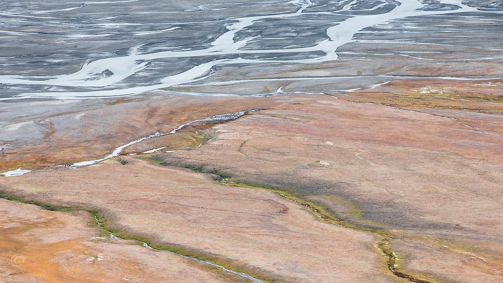 Delta renner gjennom h&oslash;stfarget landskap i Adventsdalen, Spitsbergen, Svalbard.<br /> <br /> Delta running through autumn colours in Adventsdalen east of Longyearbyen on Spitsbergen, Svalbard, Norway. August.