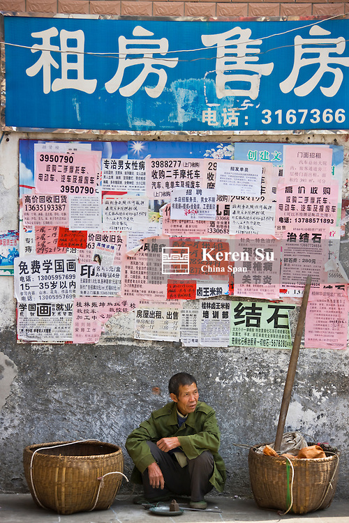 Man by wall with posters, Guilin, Guangxi, China
