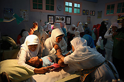 A young girl screams while being circumcised in Bandung, Indonesia on April 23, 2006. The families of 248 girls were given money to have their children circumcised in a mass circumcision celebration timed to honour the Prophet Mohammed's birthday. While religion was the main reason for circumcisions, it is believed by some locals that a girl who is not circumcised would have unclean genitals after she urinates which could lead to cervical cancer. It is also believed if one prays with unclean genitals their prayer won't be heard. The practitioners used scissors to cut the hood and tip of the clitoris. The World Health Organization has deemed the ritual unnecessary and condemns such practices.