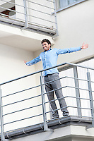Full length of smiling young businessman standing arms outstretched at hotel balcony