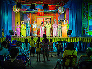 """06 DECEMBER 2015 - BANGKOK, THAILAND: People watch a Chinese opera performance at the Ruby Goddess Shrine in the Dusit district of Bangkok. Chinese opera was once very popular in Thailand, where it is called """"Ngiew."""" It is usually performed in the Teochew language. Millions of Chinese emigrated to Thailand (then Siam) in the 18th and 19th centuries and brought their culture with them. Recently the popularity of ngiew has faded as people turn to performances of opera on DVD or movies. There are about 30 Chinese opera troupes left in Bangkok and its environs. They are especially busy during Chinese New Year and Chinese holidays when they travel from Chinese temple to Chinese temple performing on stages they put up in streets near the temple, sometimes sleeping on hammocks they sling under their stage.     PHOTO BY JACK KURTZ"""