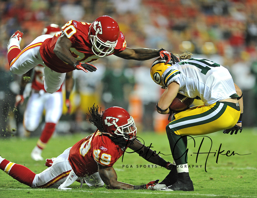 ESPN The Magazine -- Wide receiver Brett Swain #16 of the Green Bay Packers after making a catch for a first down finds his forward progress thwarted by a two pronged D-back attack by Kendrick Lewis #49 by land and Javier Arenas #30 by air of the Kansas City Chiefs, in a 17-13 Chiefs preseason win at Arrowhead Stadium in Kansas City, Missouri.  ..