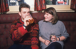 Couple sitting at table in pub drinking and smiling,