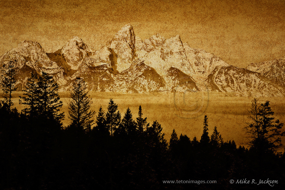 Sunrise on the Grand Tetons with low valley fog and silhouettes of spruce and pines in Jackson Hole, WY.