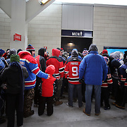 Men queue for the Men's toilet at Yankee Stadium during the New York Rangers Vs New Jersey Devils NHL regular season game held outdoors at Yankee Stadium, The Bronx, New York, USA. 26th January 2014. Photo Tim Clayton