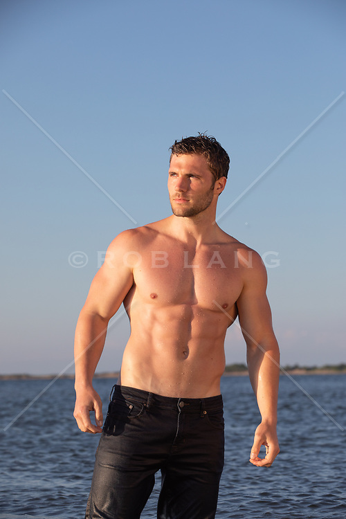 hot shirtless man in wet jeans standing in water