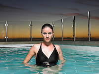 Woman standing in outdoor swimming pool at sunset