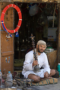 The old Souk, in Sanaa. Shop keeper at entrance  to his store that repairs & sells water pipes.