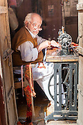 Old man with glasses sewing with sewing machine in India.