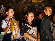 26 FEBRUARY 2017 - BANGKOK, THAILAND:  People holding photos of Bhumibol Adulyadej, the Late King of Thailand, line up in Wat Phra Kaew to pay respects to the revered monarch. Thousands of Thais continue to line up in Wat Phra Kaew at the Grand Palace in Bangkok daily to pay respects to Bhumibol Adulyadej, the Late King of Thailand, who died on 13 October 2016. The government set a year long mourning period for the revered King, who will be cremated in late 2017.       PHOTO BY JACK KURTZ