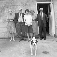 People and dog in front of house.<br />