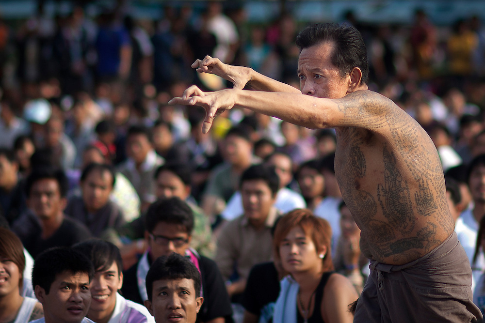 A devotee in deep trance clenches his fingers as he make his way to the shrine on the ground of Bang Phra Buddhist temple during Sak Yant religious festival  on Saturday, March. 03, 2012 in Nakhon Chaisi, Thailand. Thais come from all over Thailand to be tattooed by the temple's monks on their bodies being inked by hand using a long metal stylus. The religious tattoos are believed to be protection from ghost and bad spirits...
