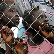 100119-N-5345W-170.BONEL, Haiti (Jan. 19, 2010).Local Haitian children watch from behind a fence as U.S. Navy and Marine relief forces move heavy equipment into position while establishing an operating base within the New Hope Mission compound in Bonel, Haiti. The multi-purpose amphibious assault ship USS Bataan (LHD 5) is on station in Haiti along with the amphibious dock landing ships USS Fort McHenry (LSD 43), USS Gunston Hall (LSD 44), and USS Carter Hall (LSD 50) as the Bataan Amphibious Relief Mission in support of Operation Unified Response, a joint operation providing military support capabilities to civil authorities to help stabilize and improve the situation in Haiti following a 7.0 magnitude earthquake that devastated the island nation. (U.S. Navy photo by Mass Communication Specialist 2nd Class Kristopher Wilson/Released)