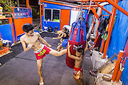 "18 DECEMBER 2104 - BANGKOK, THAILAND: A boxer works out by kicking the heavy bag at the Kanisorn gym. The Kanisorn boxing gym is a small gym along the Wong Wian Yai - Samut Sakhon train tracks. Young people from the nearby communities come to the gym to learn Thai boxing. Muay Thai (Muai Thai) is a Thai fighting sport that uses stand-up striking along with various clinching techniques. It is sometimes known as ""the art of eight limbs"" because it is characterized by the combined use of fists, elbows, knees, shins, being associated with a good physical preparation that makes a full-contact fighter very efficient. Muay Thai became widespread internationally in the twentieth century, when practitioners defeated notable practitioners of other martial arts. A professional league is governed by the World Muay Thai Council. Muay Thai is frequently seen as a way out of poverty for young Thais and Muay Thai camps and schools are frequently crowded. Muay Thai professionals and champions are often celebrities in Thailand.     PHOTO BY JACK KURTZ"