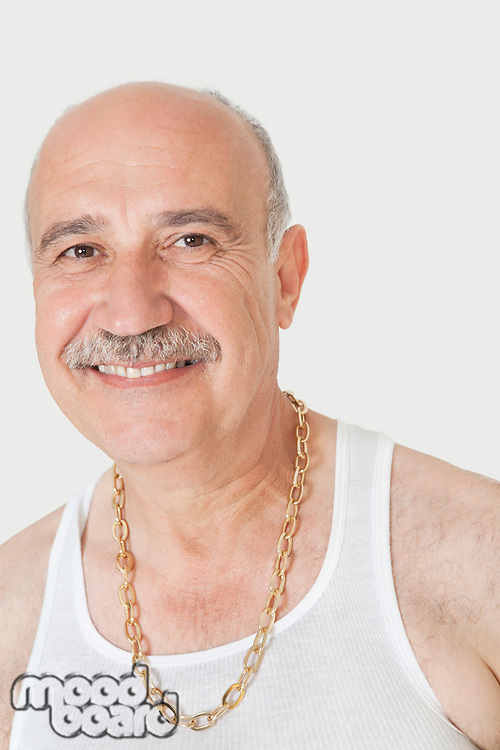 Portrait of happy senior man with gold chain over gray background