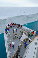 Tourists on the bow of a ship approaching the face of the Brasvellbreen tongue of the Austfonna ice cap on Nordaustlandet in the Svalbard archipelago, Norway.