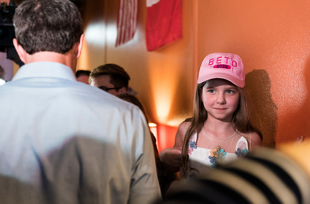 A young Beto O'Rourke supporter looks on as the candidate, left, speaks with supporters during a three day road trip across Iowa, in Mount Pleasant, Iowa, U.S., March 15, 2019.  REUTERS/Ben Brewer