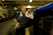 A British Airways baggage loads passengers' possessions into an airline container at Heathrow terminal 5.