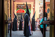 A Holy Week procession makes a stop in a commercial street. Seville, Spain