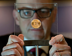 © Licensed to London News Pictures. 02/03/2012. London, UK. Peter Swanston CEO of the London Mint holding a rare American 1933 Double Eagle coin on display at Goldsmiths Hall in London for the first time. In 2002, a 1933 Double Eagle sold for 7.6 million dollars, making it the most expensive gold coin in the world to come to auction up to that time. Photo credit : Ben Cawthra/LNP