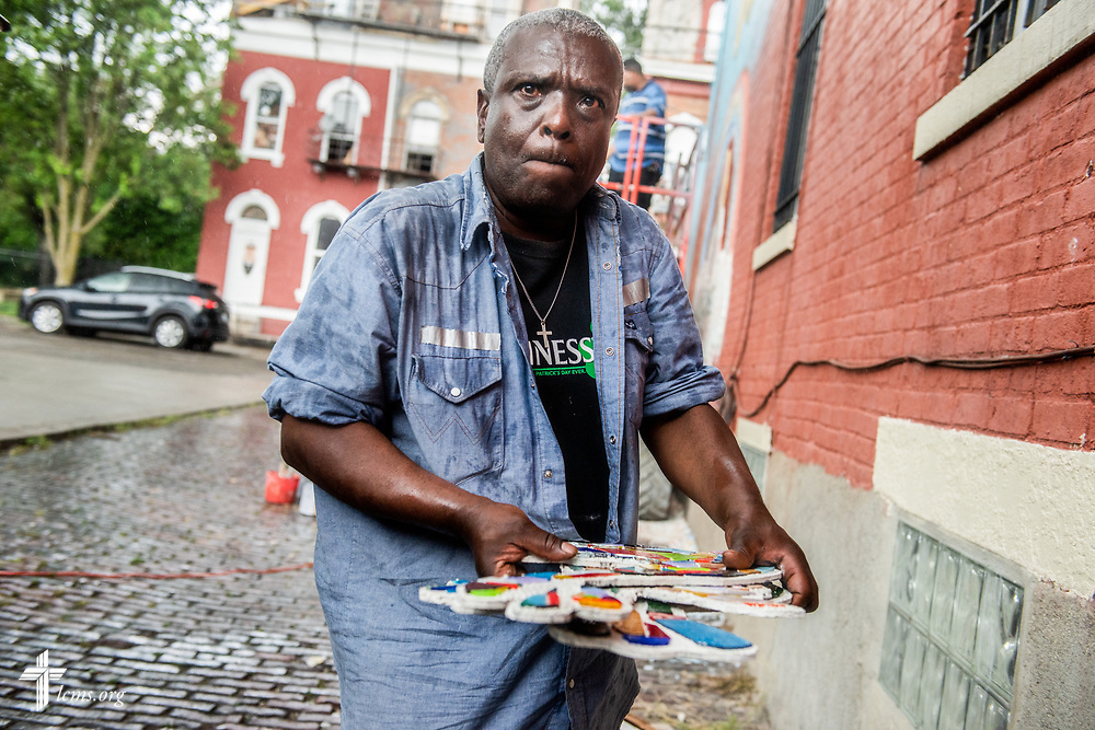 Glenn Hawkins, who attends Prince of Peace Lutheran Church in the Over-the-Rhine neighborhood of Cincinnati, helps shuttle stained glass birds to shelter after a torrential rain shower thwarted the day's work on the new mural on the side of Victoria's House of Hope, a transitional housing apartment building that is part of The Welcome Home Collaborative program, on Wednesday, May 16, 2018, in Cincinnati. Victoria, a young woman who volunteered her time at Prince of Peace Lutheran Church, made a wish to the Make-a-Wish Foundation to rehab the old building before she died of a brain tumor. Artist Rachel Ziegler designed the mural and had attendees of the church and external community assist with the construction. LCMS Communications/Erik M. Lunsford