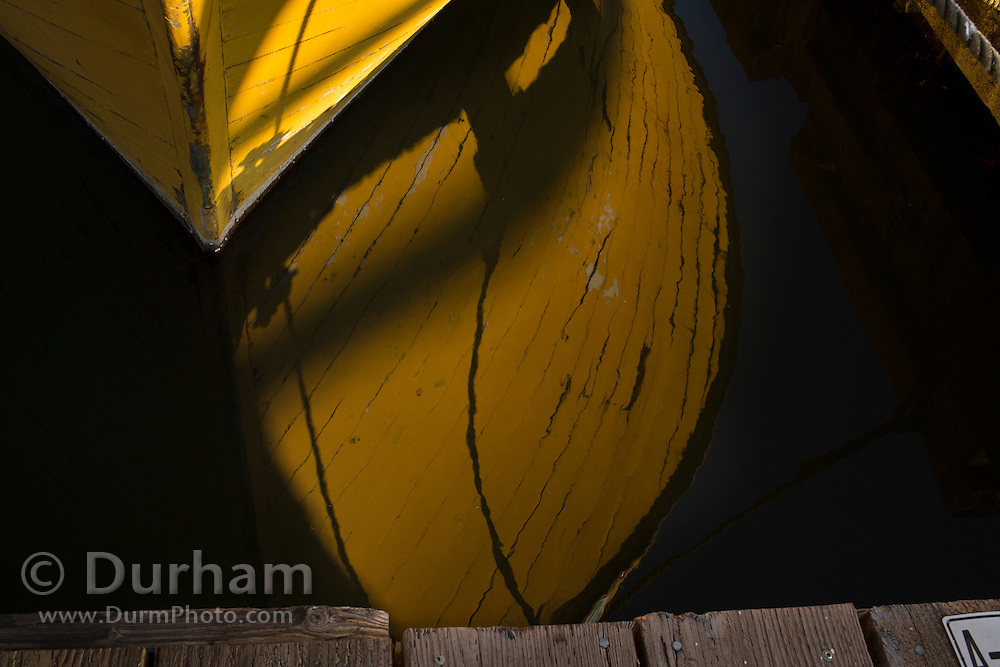 An abondoned boat is reflected in the water along the Giribaldi pier. Oregon Coast.
