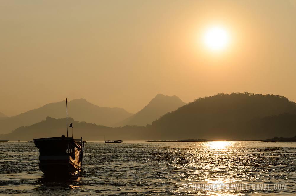 A beautiful golden sunset on the Mekong River near Luang Prabang in central Laos. Moutnains and hills are silhouetted in the distance, and a wooden sampan is in the bottom left of frame.