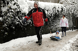 © under license to London News Pictures. 1.12.2010 Snow chaos in Orpington in Kent.  Phil Edmeads pulling son Samuel age 2  with mum Natalie at the back..Walking up Station Road near Orpington Station, Kent. Picture credit should read Grant Falvey/London News Pictures
