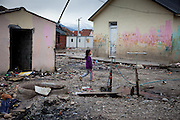 A girl walking the area of Konik Camp located in the suburbs of the city of Podgorica, Montenegro. A huge fire in 2012 detroyed a big part of the refugee camp and many of the inhabitants are living in containers. The housing pictured belongs still to the part with old housing facilities.