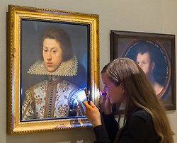 London, July 3rd 2017. A Bonhams gallery worker examines William Larkin's Portrait of Thomas Pope, estimated to fetch between £40-60,000 in their forthcoming Old Master Paintings sale.