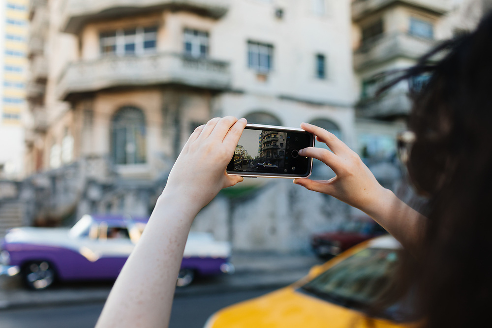 20 something takes cell phone photo outside Hotel Nacional de Cuba in Havana, Cuba