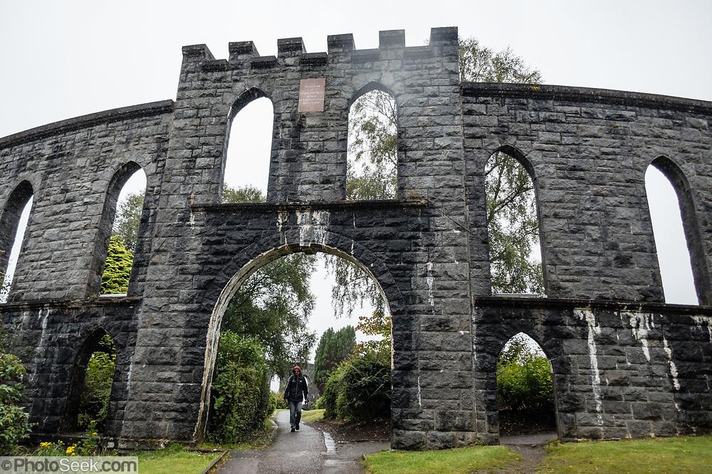 McCaig's Tower rises prominently on Battery Hill overlooking the town of Oban in Argyll, Scotland, United Kingdom, Europe. It is built of Bonawe granite with a circumference of 200 meters with two-tiers of 94 lancet arches. The structure was commissioned by the wealthy, philanthropic banker (North of Scotland Bank), John Stuart McCaig, his own architect. The tower was built between 1897 and his death in 1902, intended as a lasting monument to McCaig's family and as employment for local stonemasons during winter. As an admirer of Roman and Greek architecture, McCaig had planned for an elaborate structure based on the Colosseum in Rome, but only the outer walls were completed. Oban is an important tourism hub and Caledonian MacBrayne (Calmac) ferry port, protected by the island of Kerrera and Isle of Mull, in the Firth of Lorn.