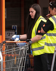 © Licensed to London News Pictures. 27/04/2020. Watford, UK. A member staff disinfecting shopping trolley handles for customers at B&Q in Watford, Hertfordshire. British Prime Minister Boris Johnson has warned the public against relaxing lockdown precautions too soon. Photo credit: Ben Cawthra/LNP