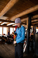 A female skier folds her climbing skins while inside the  Peter Estin hut in Colorado.  Hut tours are very popular in Colorado where you enjoy warmth, safety and plenty of ammenities while in the backcountry.