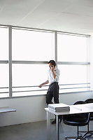Business man using mobile phone looking out of office window