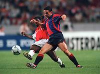 Marc Overmars (Barcelona) tackled by Lauren (Arsenal). Arsenal v FC Barcelona, The Amsterdam Tournament, Amsterdam Arena, Holland, 3/8/2000. Credit Colorsport / Stuart MacFarlane.