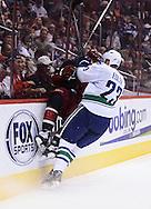 Nov 5, 2013; Glendale, AZ, USA; Vancouver Canucks defensemen Alexander Edler (23) checks Phoenix Coyotes forward Paul Bissonnette (12) in the second period at Jobing.com Arena. Mandatory Credit: Jennifer Stewart-USA TODAY Sports