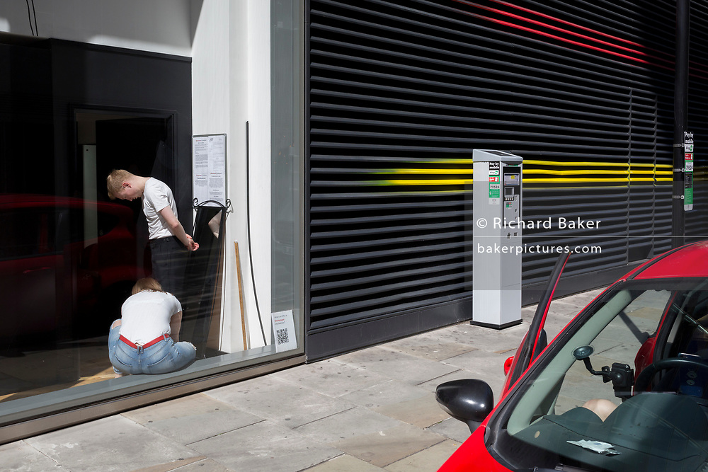 A male customer has the length of his trousers checked in the wondow of Shirststream, a dry cleaners and clothing alterations business on Bread Street in the City of London, the capital's financial district (aka the Square Mile), on 22nd August 2019, in London, England.