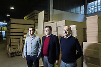 SOVERIA MANNELLI, ITALY - 16 NOVEMBER 2016: (L-R) Siblings Francesco, Angelo and Claudio Sirianni, who run the family business Camillo Sirianni, a school furniture manifacturer, pose for a portrait in the company's warehouse in Soveria Mannelli, Italy, on November 16th 2016.<br /> <br /> Camillo Sirianni is a third generation family business that started as a family mechanized carpentry in 1909 and transformed into a leading school furniture manufacturer. In a high-tech warehouse in the outskirts of Soveria Mannelli, they assemble thousands of Calabrian beechwooden, colorful desks, benches, closets and other accessories that are later shipped to many corners of the globe, from the United Kingdom to the Emirates, from central America to Polynesia.<br /> <br /> Soveria Mannelli is a mountain-top village in the southern region of Calabria that counts 3,070 inhabitants. The town was a strategic outpost until the 1970s, when the main artery road from Naples area to Italy's south-western tip, Reggio Calabria went through the town. But once the government started building a motorway miles away, it was cut out from the fastest communications and from the most ambitious plans to develop Italy's South. Instead of despairing, residents benefited of the geographical disadvantage to keep away the mafia infiltrations, and started creating solid businesses thanks to its administrative stability, its forward-thinking mayors and a vibrant entrepreneurship numbering a national, medium-sized publishing house, a leading school furniture manufacturer and an ancient woolen mill.
