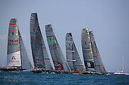 America's Cup yachts surge over start line at start of fleet race; Valencia, Spain.