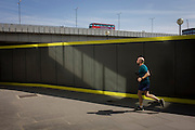 Lunchtime jogger runs past hoarding with London Bridge in the background.