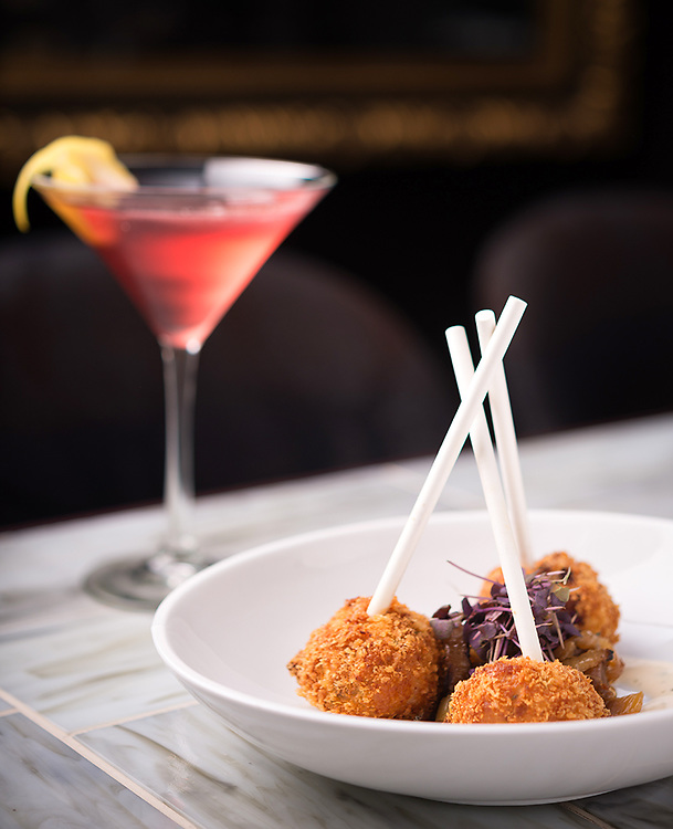 This bar scene features a cocktail and a bar dish, a trio of chicken lollipops. The context of the bar was central to this food photograph for the client, so the bar surface, chairs and artwork were lit separately from the food itself.