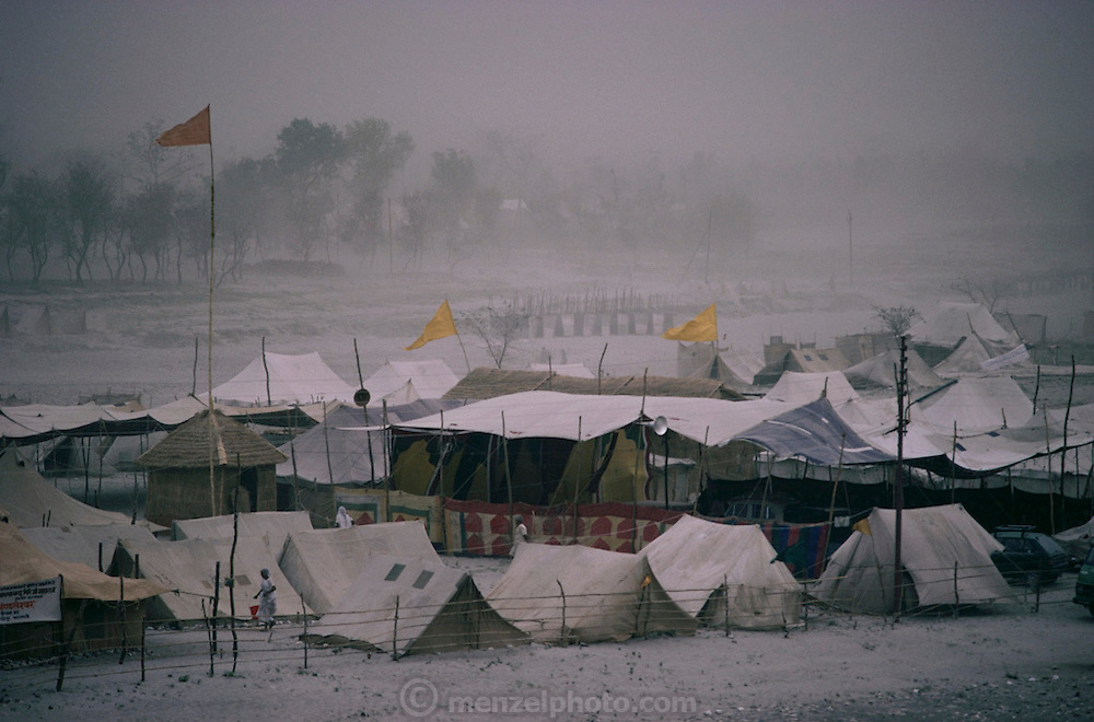 A desert dust storm whips the tents and flags of a pilgrim camp at Kumbh Mela. Every 12 years, millions of devout Hindus celebrate the month-long festival of Kumbh Mela by bathing in the holy waters of the Ganges at Hardiwar, India. Hundreds of ashrams set up dusty, sprawling camps that stretch for miles. Under the watchful eye of police and lifeguards, the faithful throng to bathe in the river.